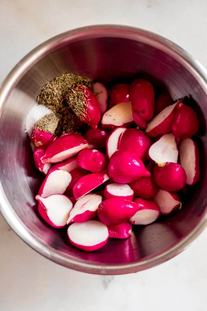 fresh halved radishes in a stainless steel bowl with dried spices