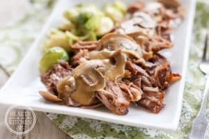 low carb pork roast with mushroom gravy on a rectangular ceramic dish served with brussel sprouts