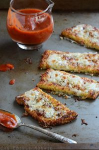 cauliflower crust garlic breadsticks on a pan with sauce
