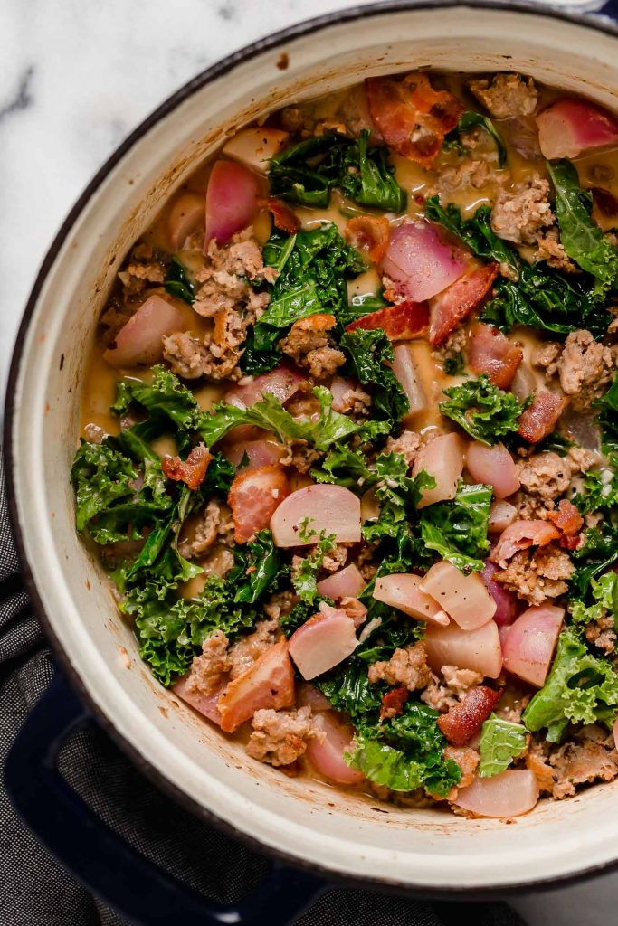 simmered soup mixed in with chopped kale and browned sausage