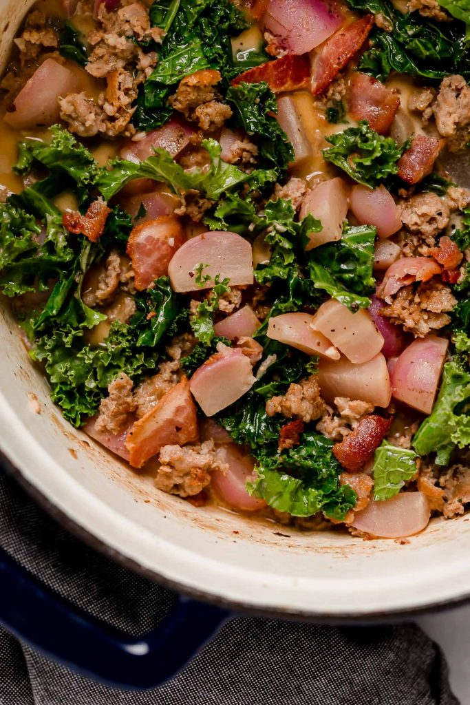 simmered soup mixed in with chopped kale, wilted, and browned sausage