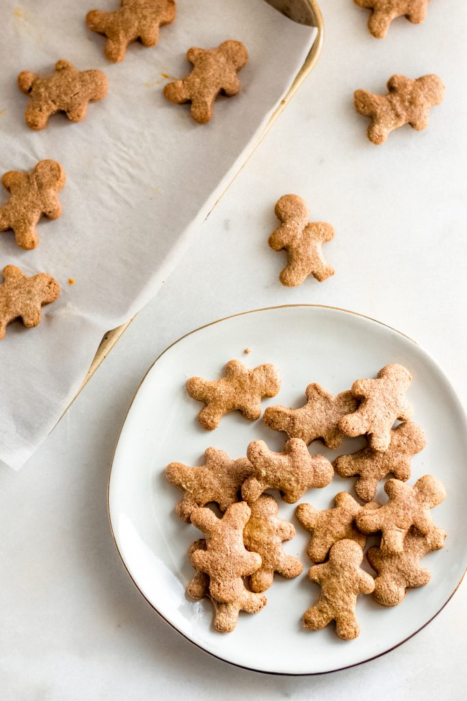 low carb gingerbread cookies transferred onto a white ceramic saucer beside baking sheet lined with parchment paper atop a marble counter