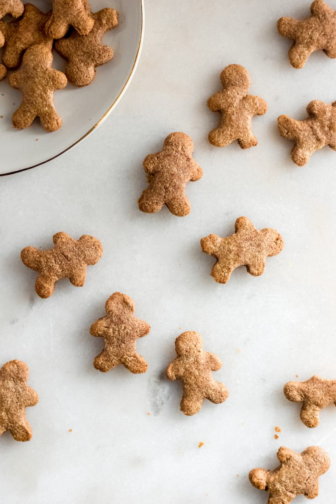 keto gingerbread cookies spread across a marble counter some on a white ceramic saucer