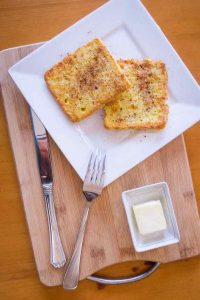 Keto French toast on square plate with silverware and butter