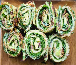 7 Bacon, Basil, & Greens Egg Roll-ups on a wooden surface