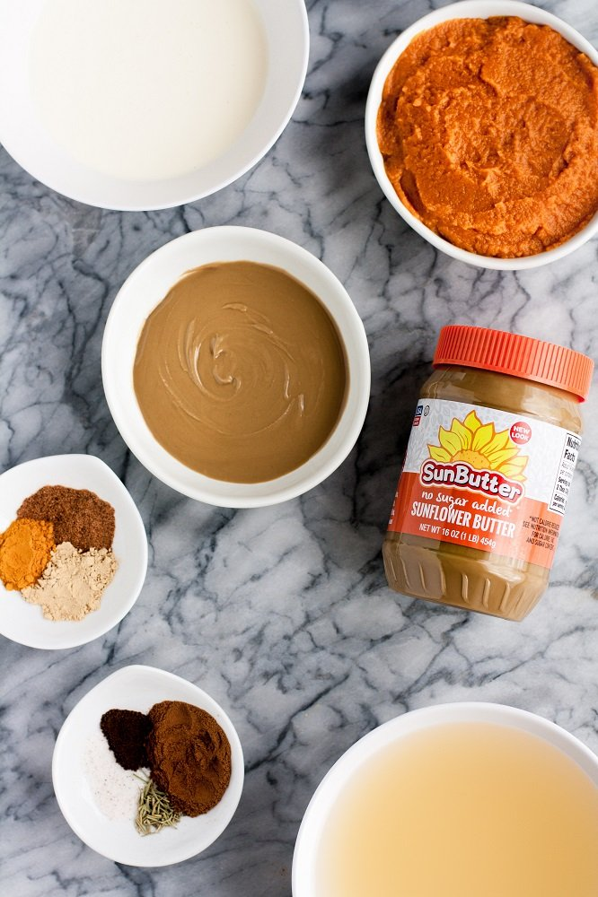 real balanced pumpkin sunbutter soup ingredients neatly laid on top of a marble kitchen counter