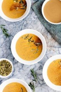 four bowls of pumpkin sunbutter soup beside a small serving of pumpkin seeds on a marble counter