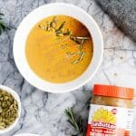 a bowl of pumpkin sunbutter soup beside a small cup of shelled pumpkin seeds and a jar of SunButter
