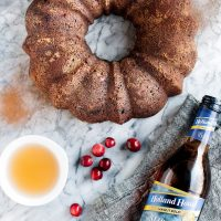 Low Carb Chocolate Cranberry Bundt Cake with Sherry Cooking Wine on top of a marble counter beside cranberries and holland house cooking wine