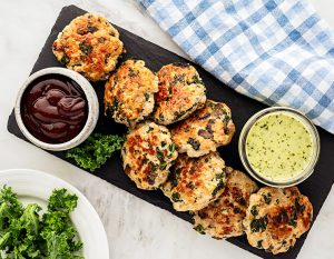 kale and mushroom sausage patties on a rectangular wooden board with 2 dip variants