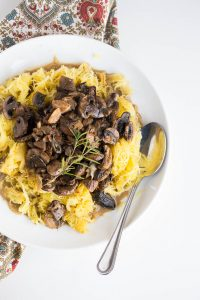 Bowl of Spaghetti squash with roasted mushrooms and garlic sauce on a patterned cloth
