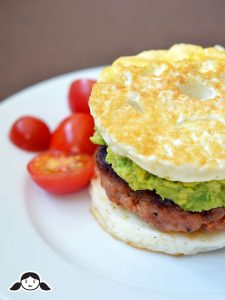 Paleo sausage egg mcmuffin with cherry tomatoes on a white plate