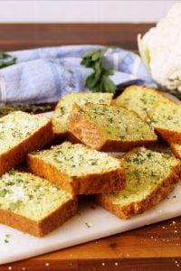 slices of cauliflower garlic bread on a cutting board