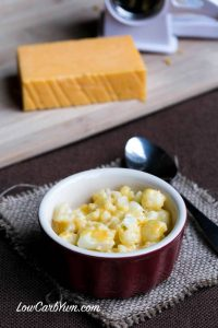 small bowl of instant cauliflower mac and cheese with spoon and cheese cube
