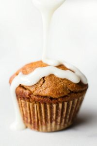 Low Carb Cinnamon Roll Muffin with icing being drizzled on it
