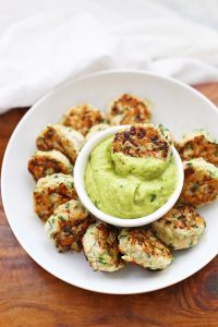 Plate of Chicken Zucchini Poppers with green avocado sauce