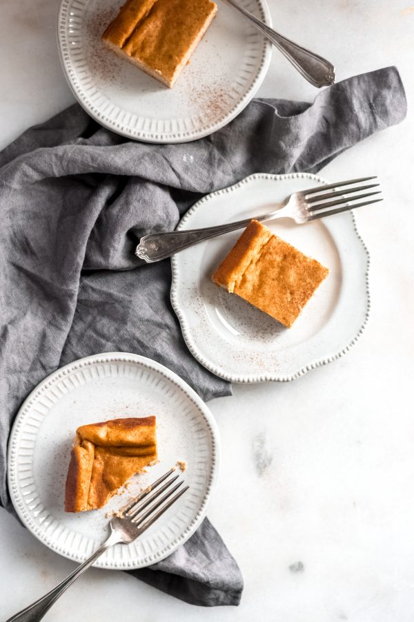 overhead shot of baked pumpkin cheesecake cut into bars in saucers with forks