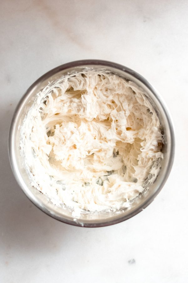 softened cream cheese mixed using an electric mixer in a stainless steel bowl