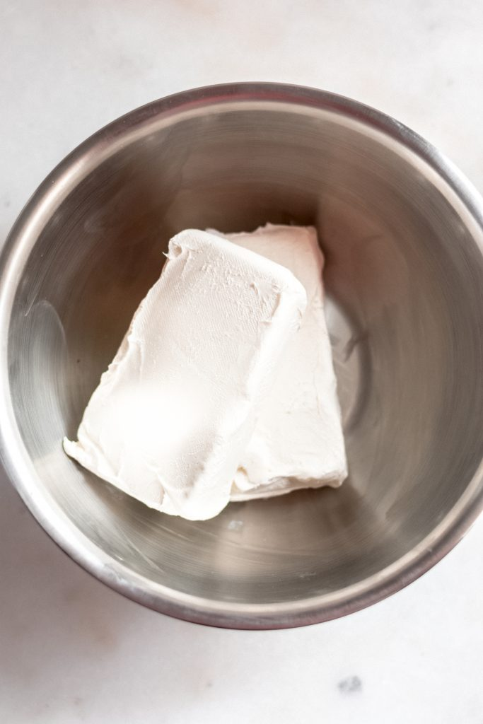 two blocks of cream cheese in a large stainless steel mixing bowl