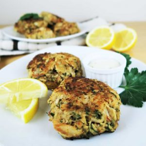 white Plate of low carb crab cakes with lemon and sauce