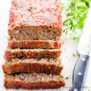 sliced Paleo Keto Low Carb Meatloaf with knife and parsley