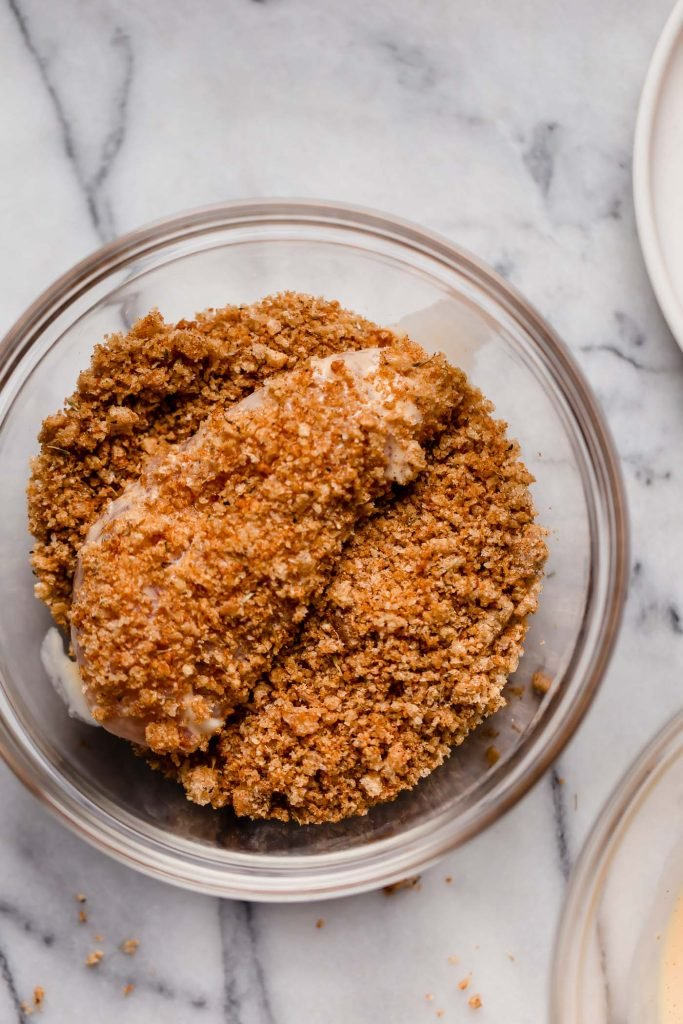 coating chicken breast with crushed pork rinds and seasoning mix