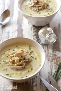 two serving bowls of Creamy Pulled Pork Soup atop a wooden counter