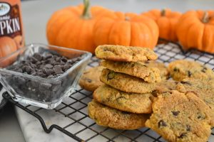 a stack of  keto pumpkin chocolate chip cookies on a cooling rack beside tiny pumpkin decor and chocolate chips