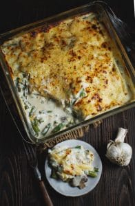 Green Bean and Mushroom Casserole in a square dish with one serving on a white plate