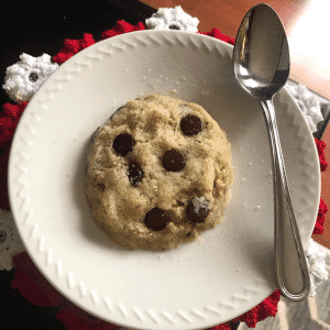 microwave chocolate chip cookie for one on a white ceramic saucer with a dessert spoon