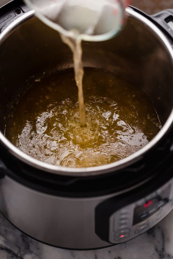 broth poured into instant pot with sauteed garlic in butter