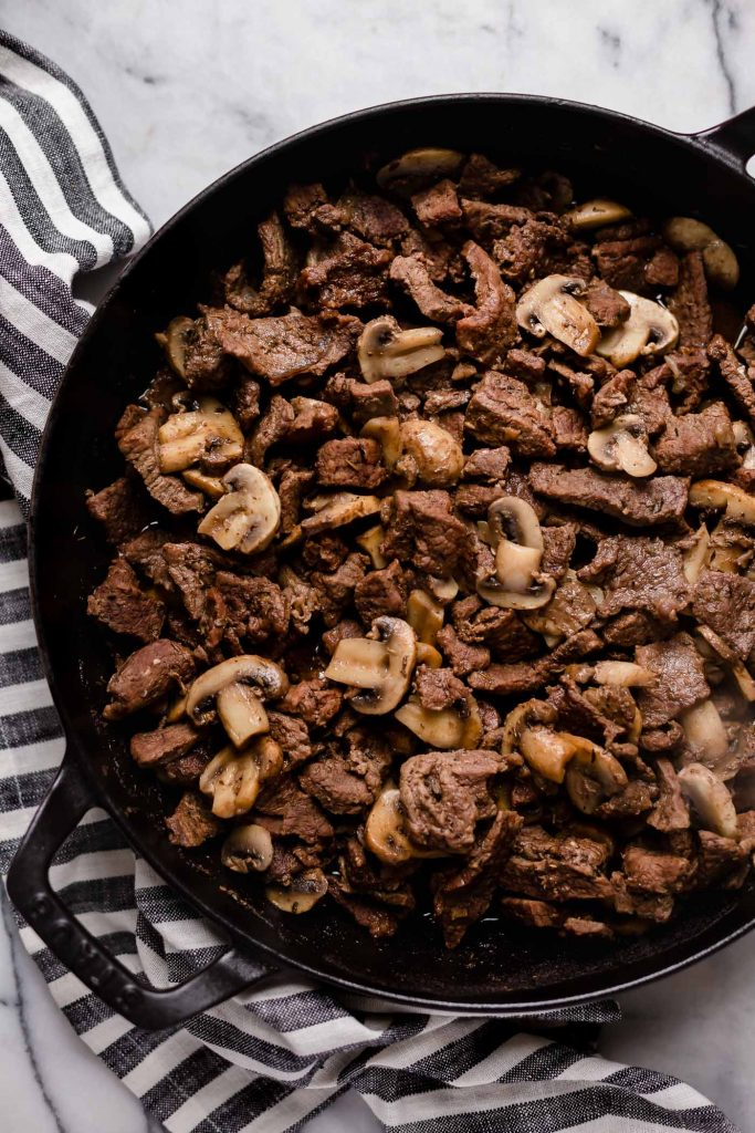 chopped seasoned and cooked beef stirred in with sliced button mushrooms in a large cast iron sauce pan