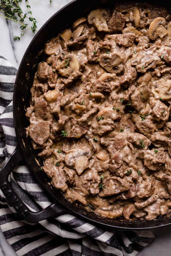 chopped seasoned and cooked beef with sliced button mushrooms and stirred-in sour cream and mayonnaise in a large cast iron sauce pan