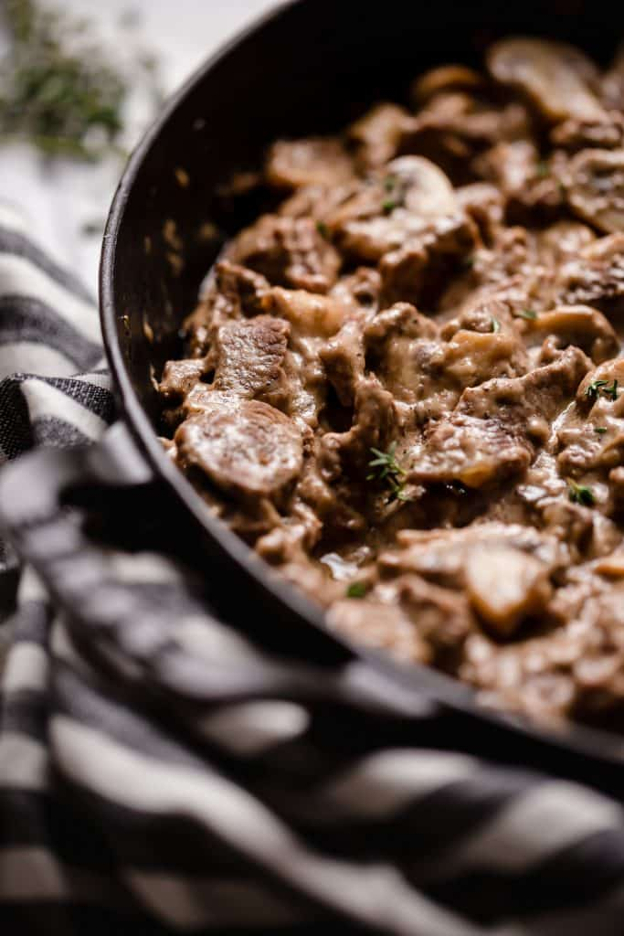 close up angled shot of keto beef stroganoff in a large cast iron sauce pan