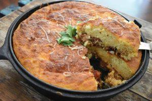Keto chicken chili cornbread casserole with slice held up