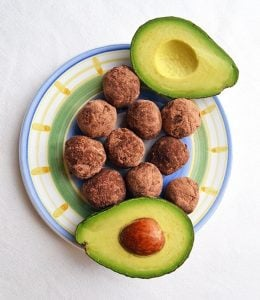 ten five minute magic keto cookie balls beside halved avocados