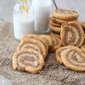piled and stacked keto cinnamon swirl cookies on burlap with milk jugs