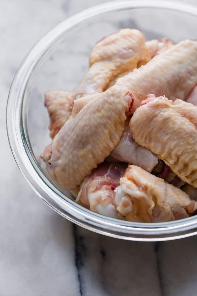 raw chicken wings in a clear glass bowl