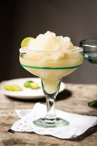 skinny frozen margarita in a salted glass with a lime wedge