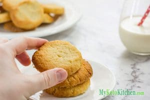 hand grabbing a cookie from a stack of 3 keto shortbread cookies