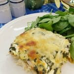 Chicken Spinach Artichoke Casserole on a plate with a bed of spinach