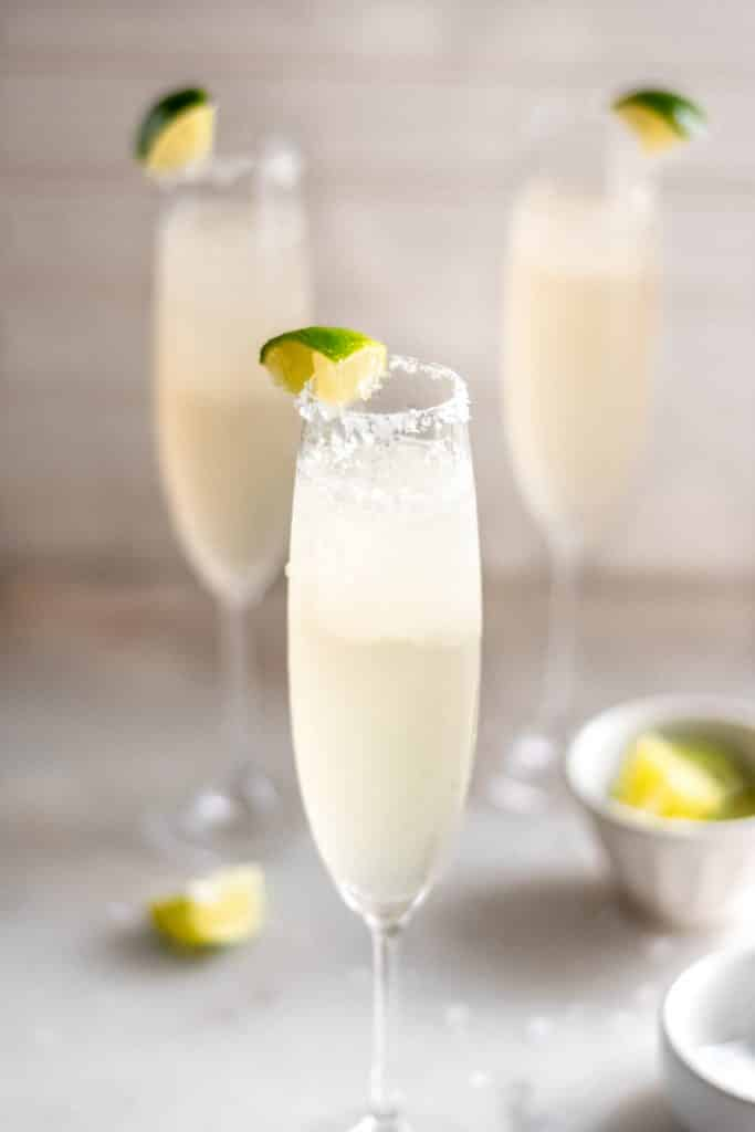 hero shot champagne margaritas in 3 champagne flutes with salt and lime wedges