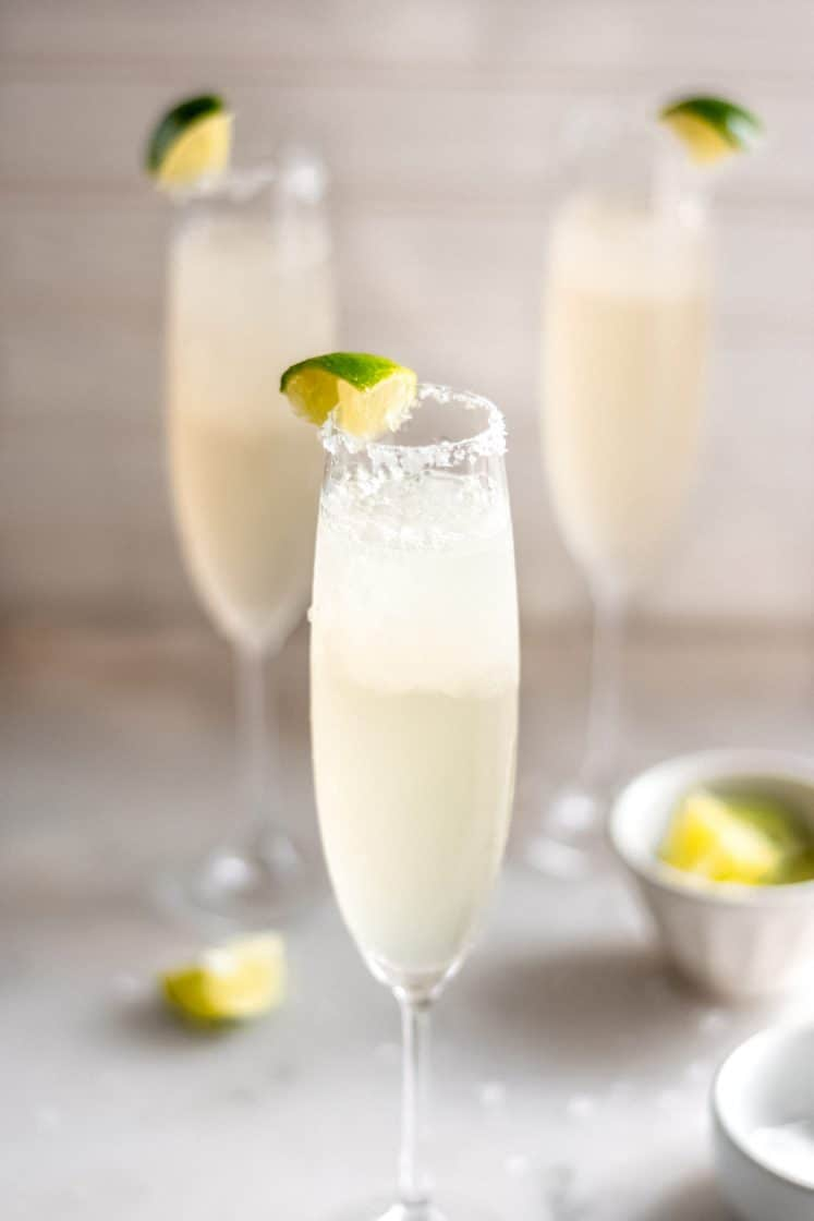 hero shot 3 servings of champagne margaritas in a champagne glass with salt and a lime wedge