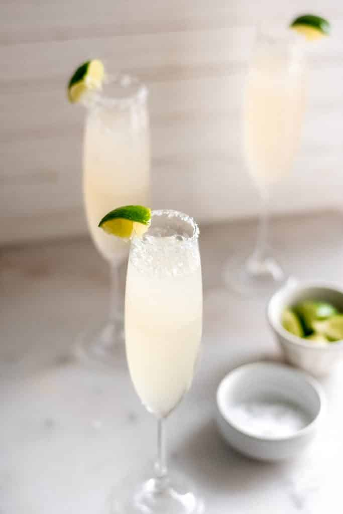 champagne margaritas in champagne flutes beside small bowls of salt and lime wedges