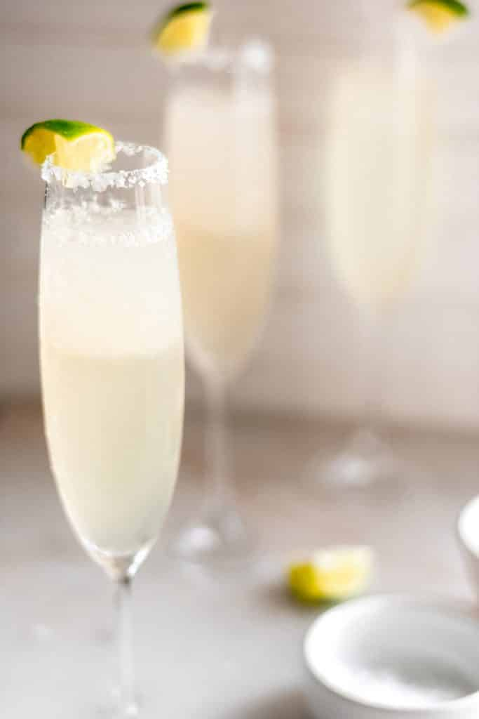 3 servings of champagne margaritas in a champagne glass with salt and a lime wedge