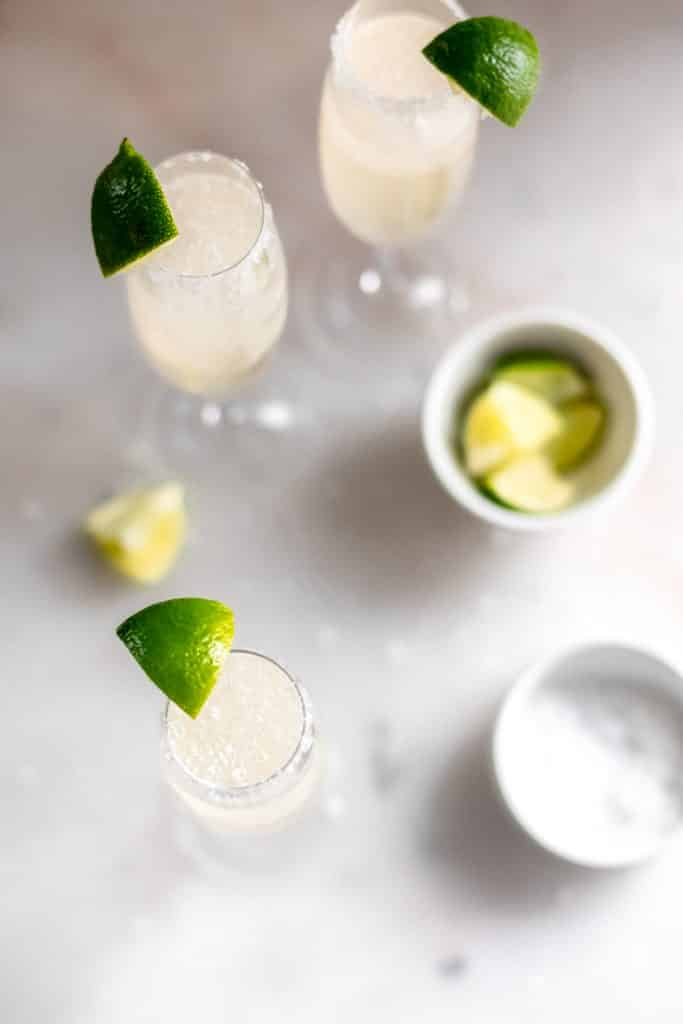 overhead shot of three champagne margaritas in 3 champagne flutes with salt and lime wedges