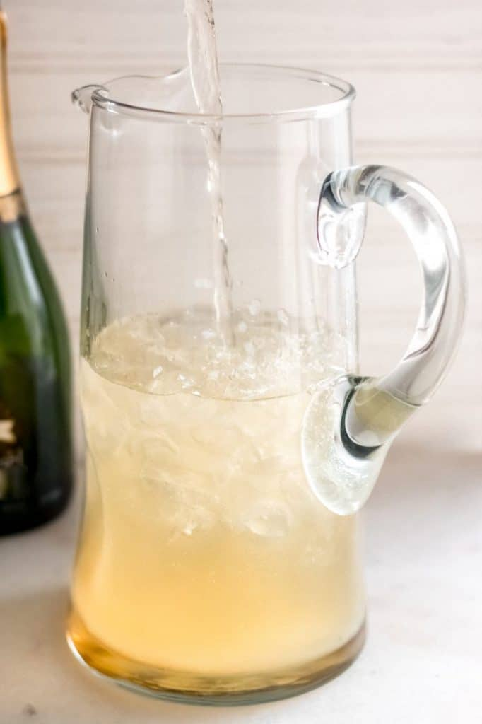 champagne margarita ingredients poured into a clear glass pitcher