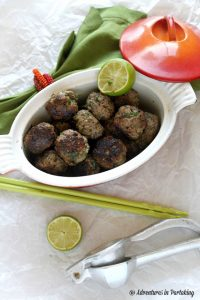 Thai Meatballs in an oval ceramic baking dish beside plastic green chopsticks and lime wedges