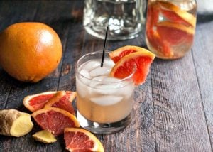 glass of grapefruit ginger fizz with grapefruit slices and ginger