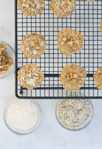 multiple keto breakfast cookies on a cooling rack with bowls of ingredients below